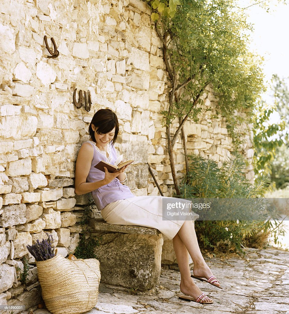 Young Woman Sits on a Stone Bench Reading a Book, Provence