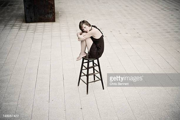 A young woman sits on a stool in a courtyard in Waterville, Maine.