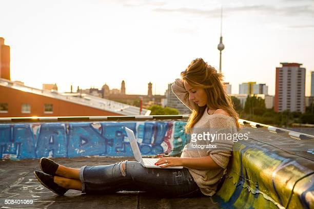 young woman sits on roof, works on laptop - back lit