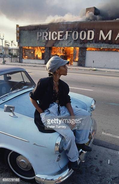 A young woman sits on the hood of a vintage automobile across the street rom a burning grocery store during the 1992 Los Angeles riots