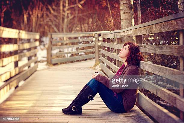 Young woman sits on wood bridge, looking at sky