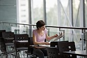 Young woman sits reading newspaper in food hall of shopping mall, Voronezh