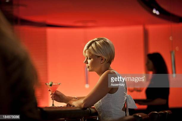 A young woman sits with her drink at a bar