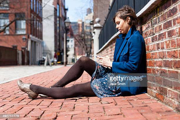 Young woman sitting against a brick wall using smartphone