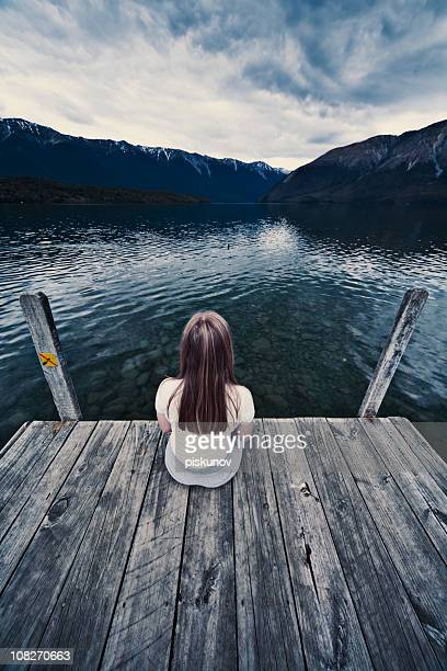 Young Woman Sitting alone on dock