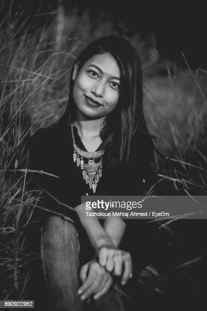 Young Woman Sitting Amidst Grass On Field