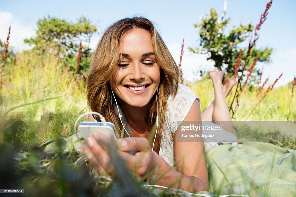 Young woman sitting among grass and using mobile phone : Foto de stock