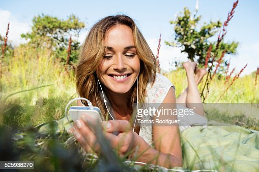 Young woman sitting among grass and using mobile phone : Stockfoto