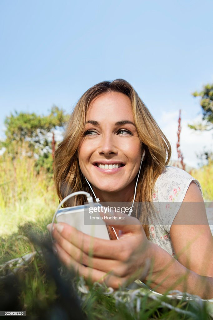 Young woman sitting among grass and using mobile phone : Stock Photo