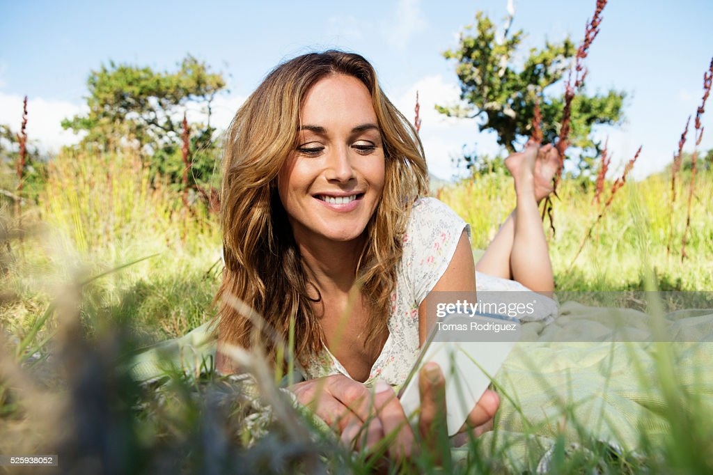 Young woman sitting among grass and using smartphone : Stock Photo