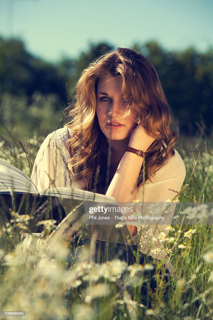 Young woman sitting amongst dasies : Stock Photo