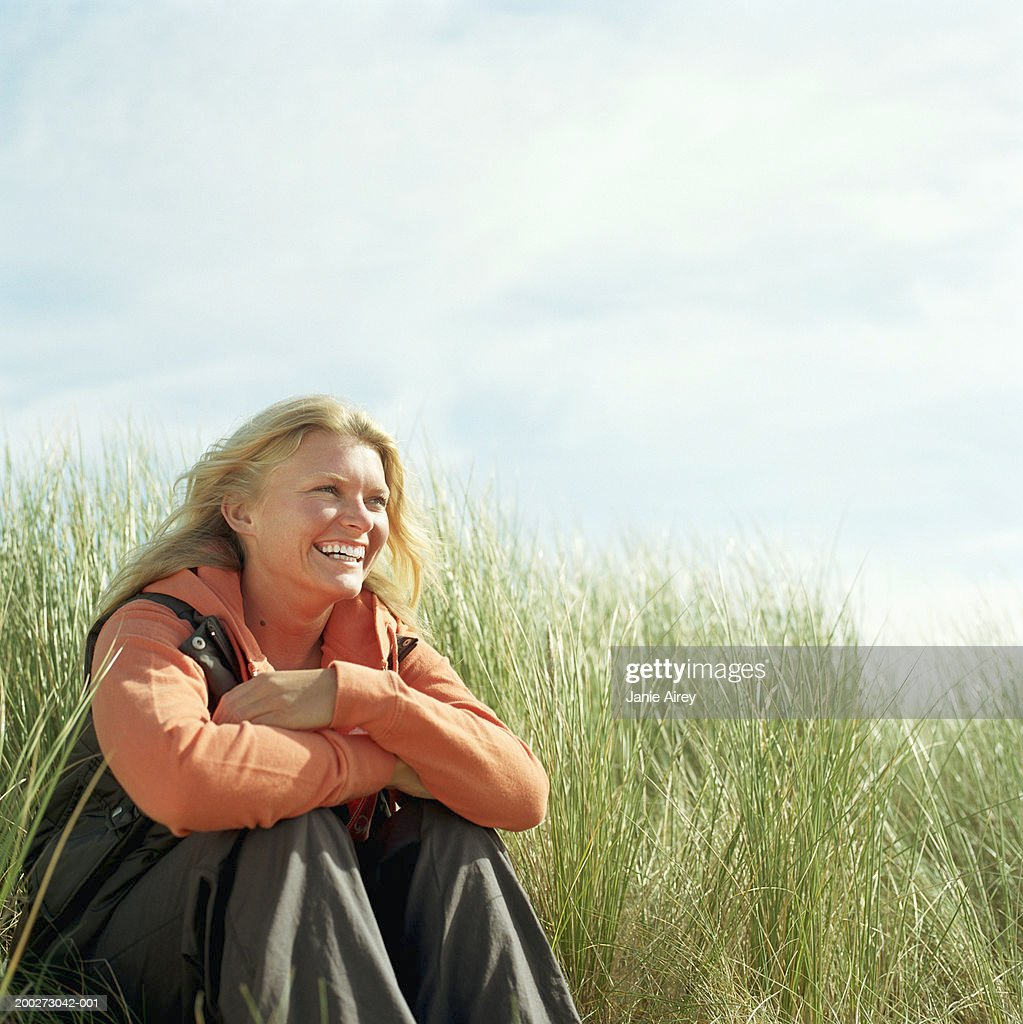 Young woman sitting amongst tall grass, smiling : Stock Photo