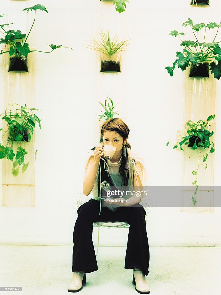 Young woman sitting and drinking beverage, potted plants decorated wall background : Stock Photo