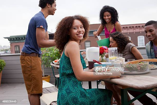 Young woman sitting at a picnic table with friends