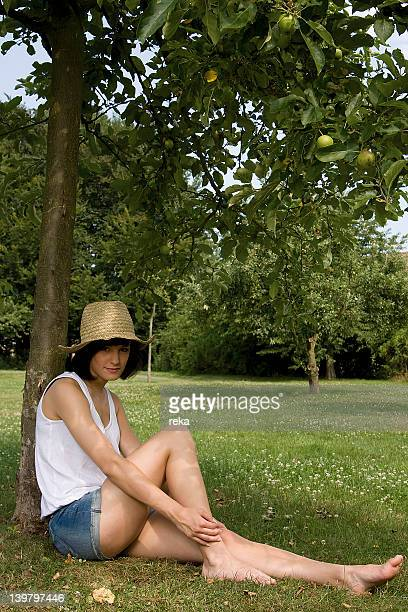 Young woman sitting at apple tree
