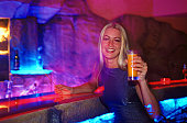Young woman sitting at bar counter holding drink, smiling