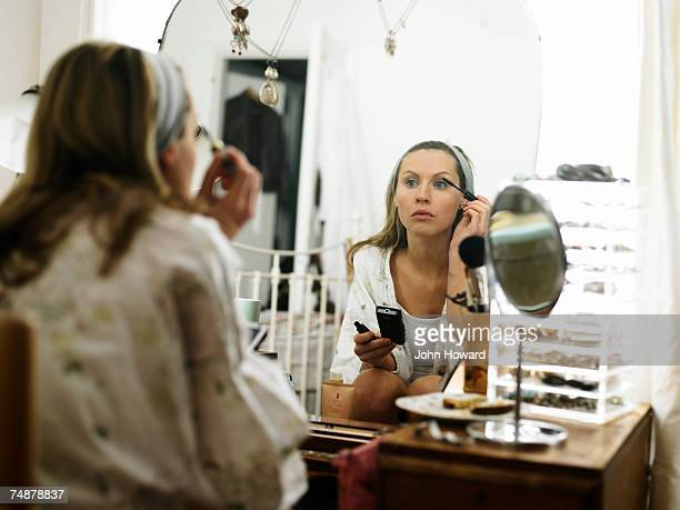 Young woman sitting at dressing table applying make-up