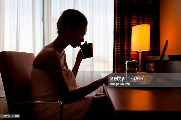 Young woman sitting at laptop in hotel room