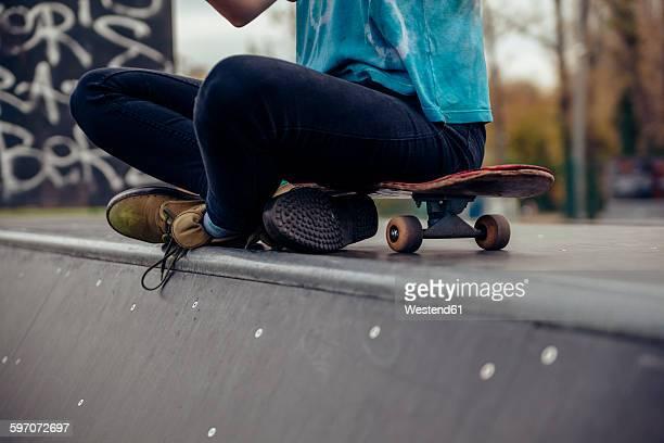 Young woman sitting at skatepark