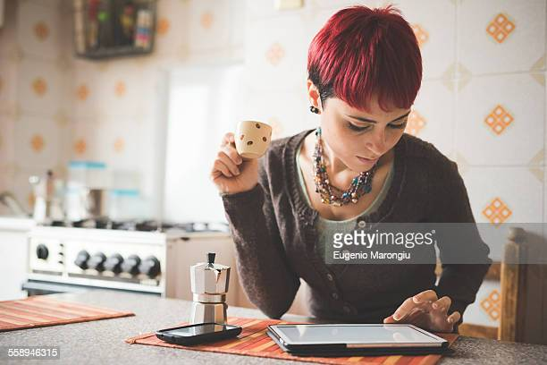 Young woman sitting at table drinking coffee, using digital tablet