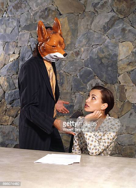 Young Woman Sitting at Table Looking at Man with Fox Mask