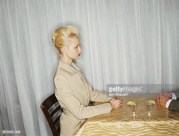 Young woman sitting at table, profile