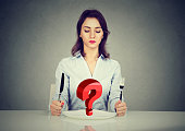 Young woman sitting at table with fork and knife looking at plate with red  question mark isolated on gray background