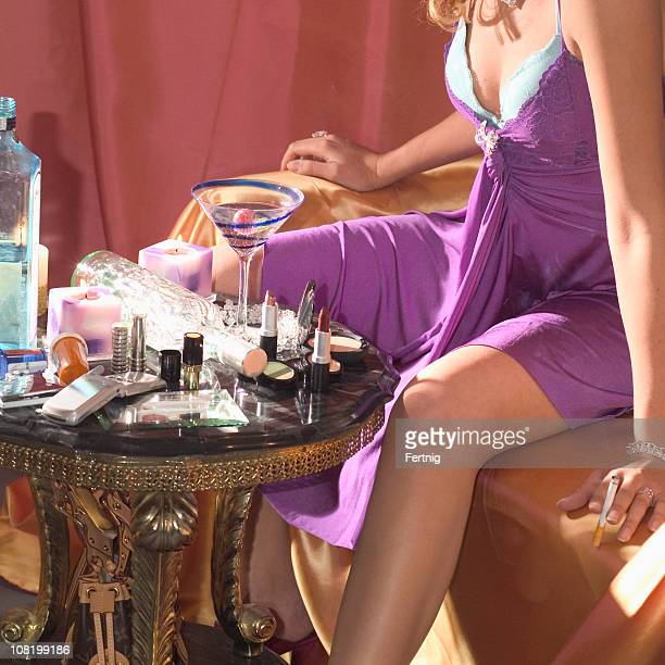 Young Woman Sitting at Table with Make-up, Alcohol and Drugs