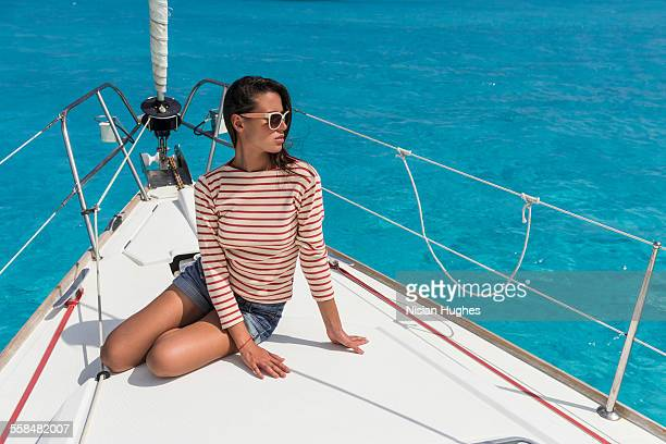 young woman sitting at the bow of sailboat