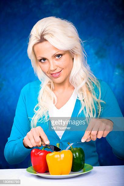 Young woman sitting at the table with bell pepper