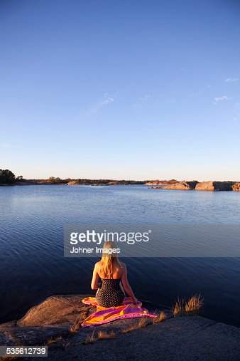 Young woman sitting at water