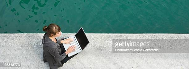 Young woman sitting beside canal, using laptop computer