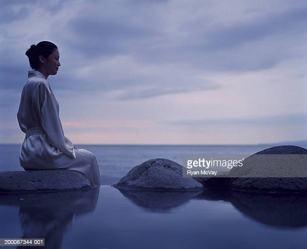 Young woman sitting beside hot spring, sea in background
