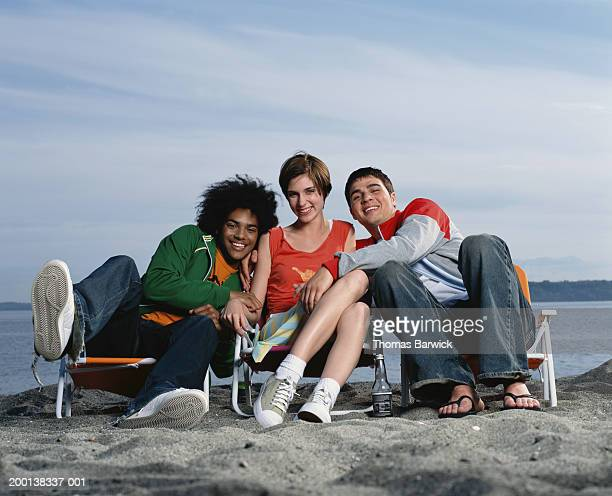 Young woman sitting between two young men on beach, portrait