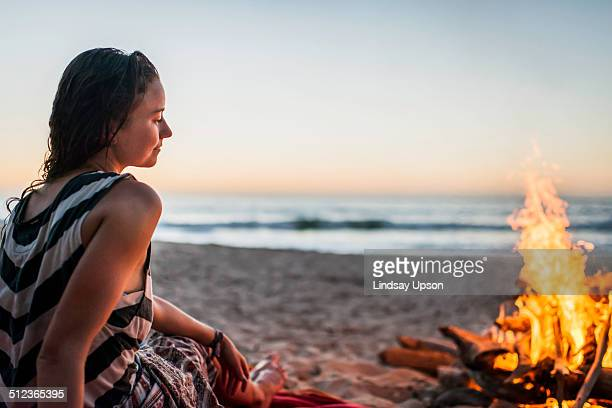 Young woman sitting by bonfire on beach
