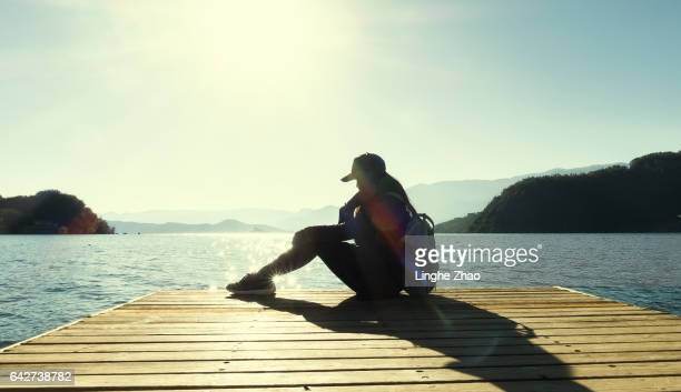 Young woman sitting by pier