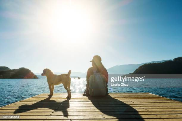 Young woman sitting by pier with dog