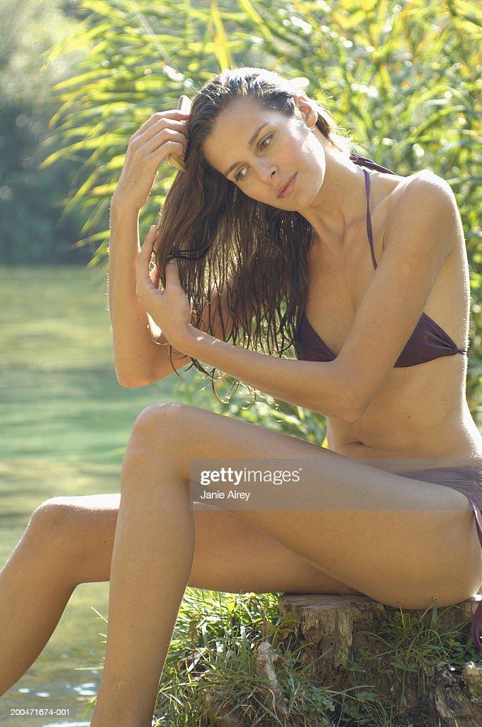 Young woman sitting by river wearing bikini, combing hair : Stock Photo