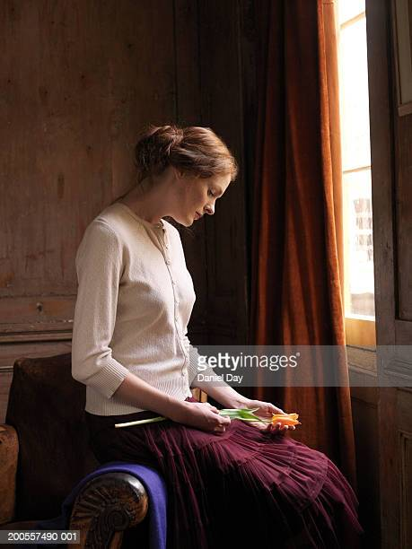 Young woman sitting by window, holding flower, side view