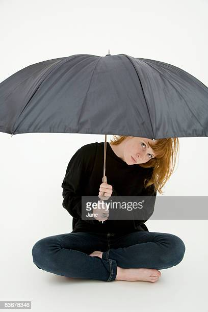 A young woman sitting cross legged under an umbrella