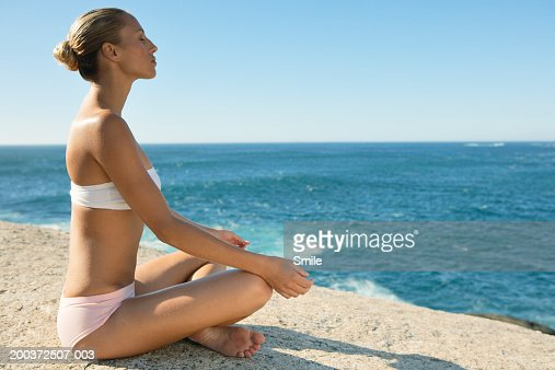 Young woman sitting cross-legged, meditating on beach, side view : Stock Photo