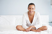 Young woman sitting cross-legged on bed, smiling, portrait
