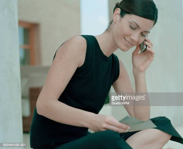 Young woman sitting cross-legged on floor using mobile phone, smiling