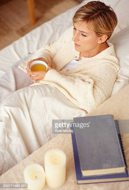Young woman sitting drinking tea on sofa in living room, elevated view