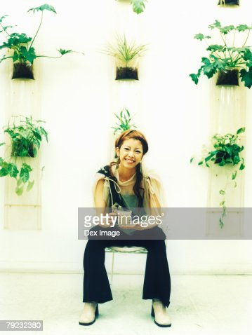 Young woman sitting holding a cup of beverage, potted plants decorated wall background : Stock Photo