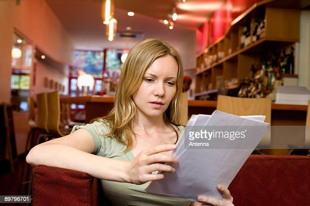 A young woman sitting in a cafe and looking at the menu