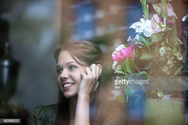 Jovem mulher sentada em um café, sorridente, vista através de vidro