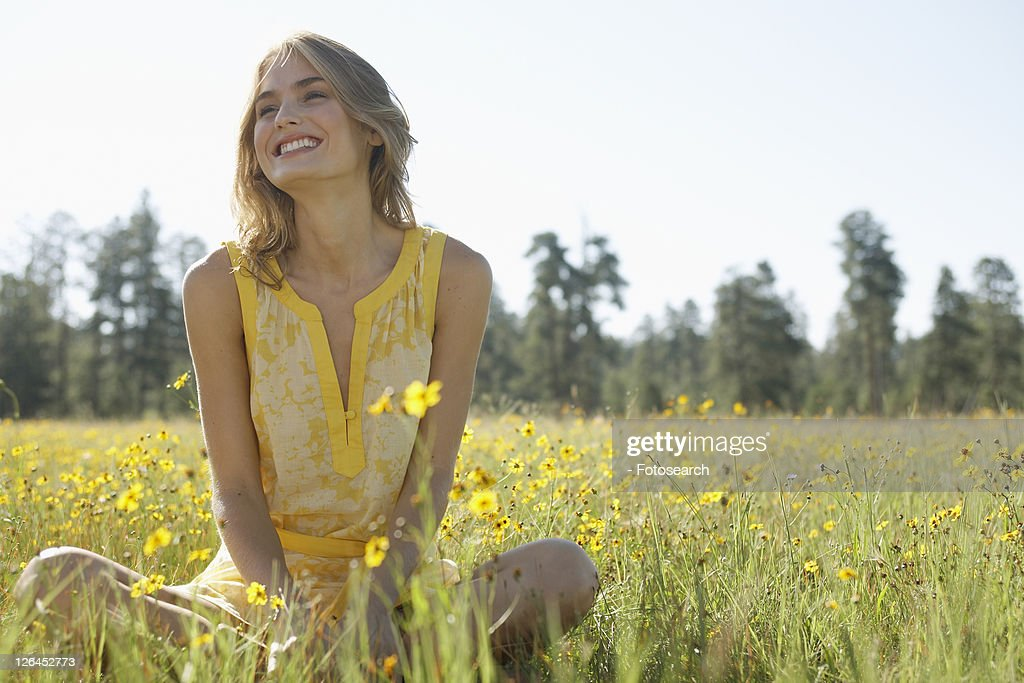 Young woman sitting in a field of wildflowers : Stock Photo