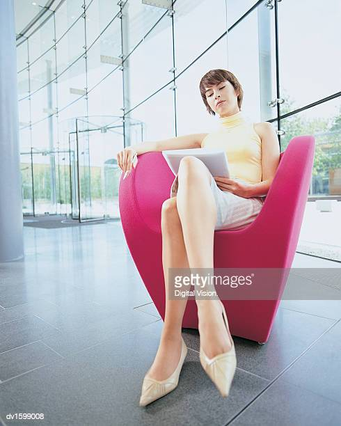 Young Woman Sitting in a Pink Armchair Reading a File and Holding a Pen