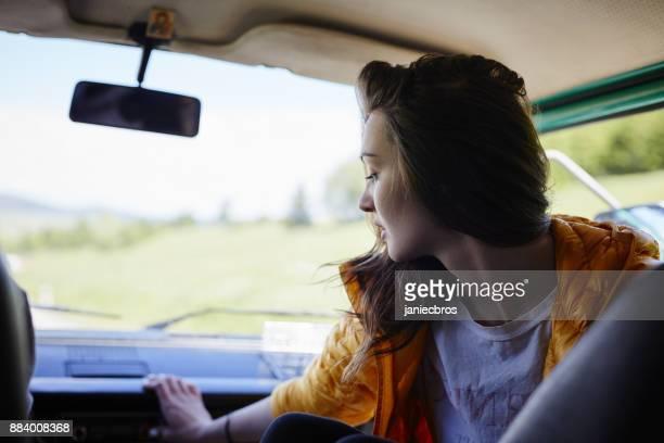 Junge Frau sitzt in einem Lieferwagen. Wanderwege zu erkunden